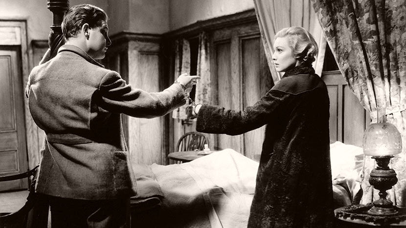On the run from the police, Richard Hannay (Robert Donat) handcuffs himself to Pamela (Madeleine Carroll).  A scene from Gaumont's 1935 film The 39 Steps