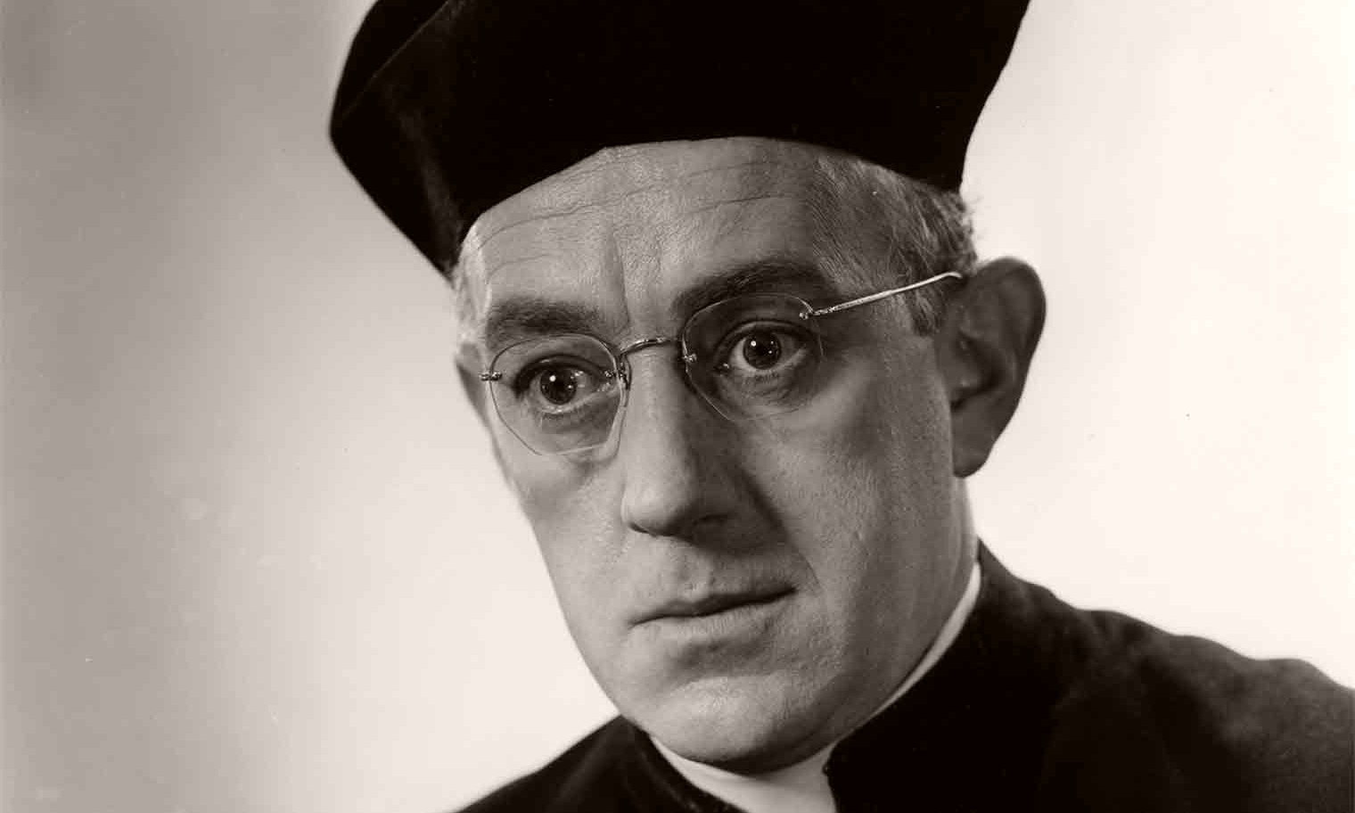 Alec Guinness, as the eponymous hero in a publicity shot for Father Brown (1954), wears glasses and a black biretta