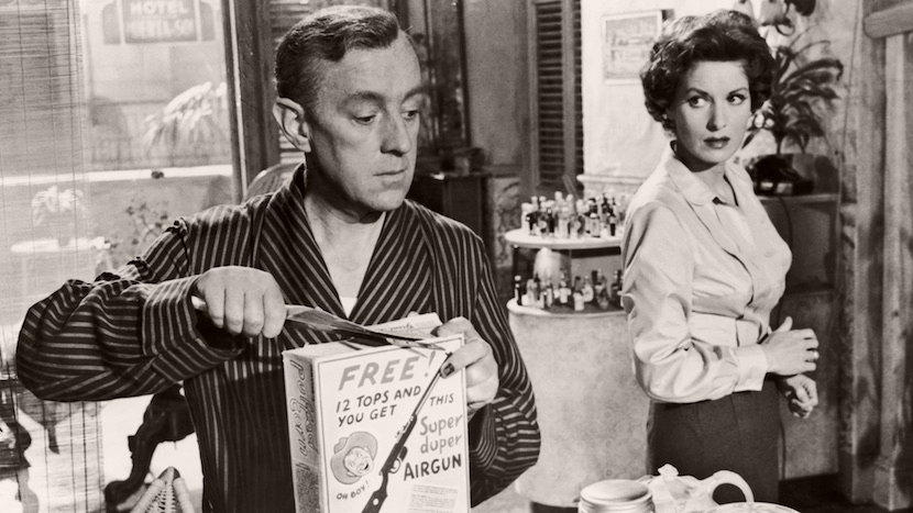Jim Wormold (Alec Guinness) opens a cereal packet as Beatrice Severn (Maureen O'Hara) watches on, in a scene from Our Man in Havana