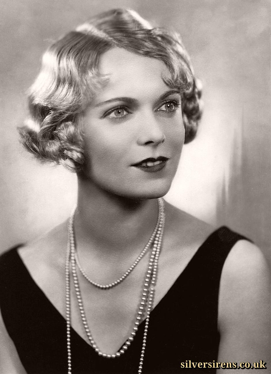 Anna Neagle, British actress, in a publicity photo wears a pearl necklace and a black dress