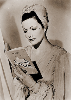 Margaret Lockwood reads a copy of Bedelia, by Vera Caspary