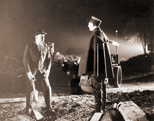 Landru is surprised at his gruesome task of burying the dismembered body of Jeanette Tissot.     He manages to convince the gendarme that he is the boss of the road gang and  is putting their poor work to rights.    Fortunately, for him, the gendarme does not look too closely into the bottom of the excavation.