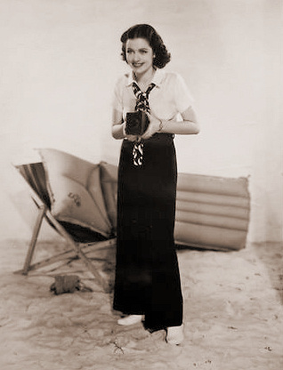 The dark-haried young beauty is none other than Margaret Lockwood, star of the new Gainsborough spy drama, The Lady Vanishes, snapped in an informal pose on the beach in her new summer slacks and white blouse of thin texture.