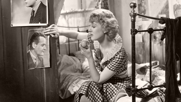 Pearl Bolton (Kay Hammond), in a gingham dress, eats an apple as she sits on her bed and looks at a pin-up photo of a male film star