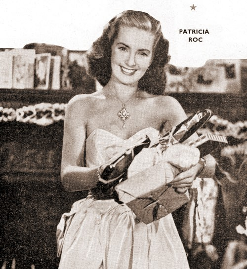 Patricia Roc in Hollywood holds her presents during the Christmas of 1949.  Behind her is a mantlepiece decorated with garlands and Christmas cards.