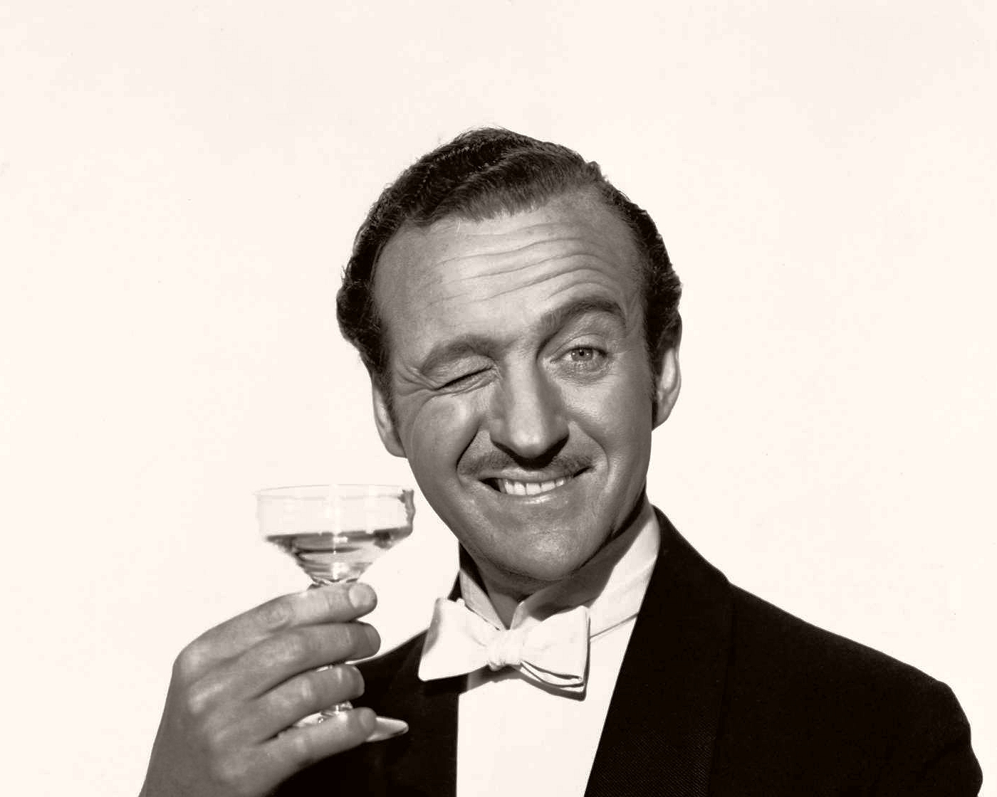 British actor David Niven, dressed in a dinner jacket an bow tie, raises a champagne coupé in a toast
