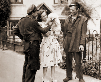 British film star Patricia Roc holds her pet dog aloft outdoors for two workmen to admire