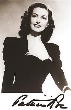 Patricia Roc smiles in an elegant black dress