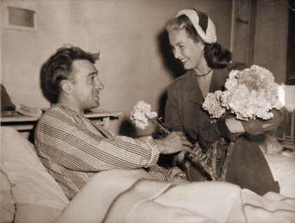 Patricia Roc smiles as she delivers flowers to a bed-bound hospital patient