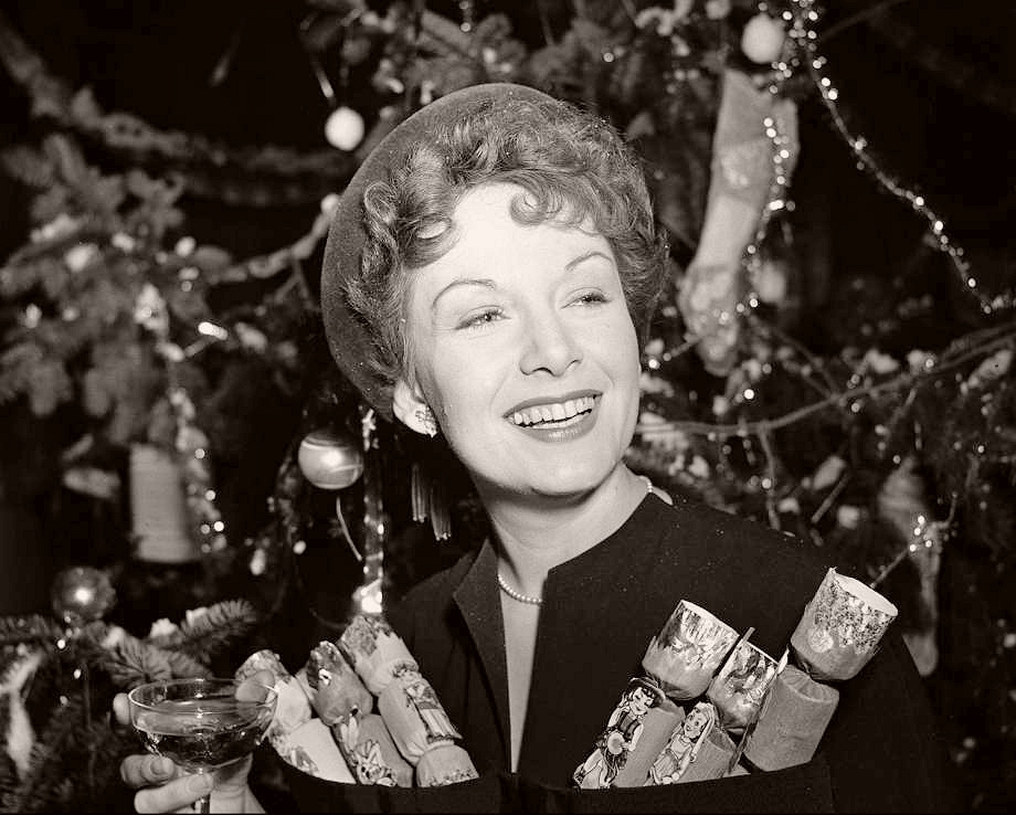 British actress Jean Kent smiles as she raises a glass of champagne. She is decorated with Christmas crackers; behind her is a Christmas tree