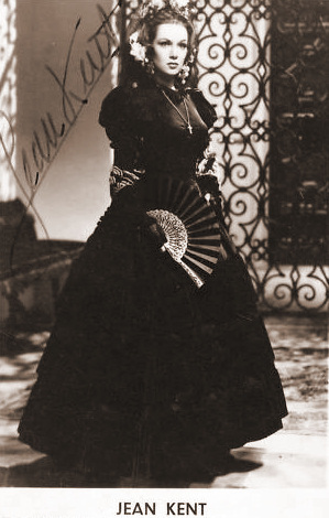 Gainsborough star Jean Kent dressed in black, holds a fan (autographed photograph)