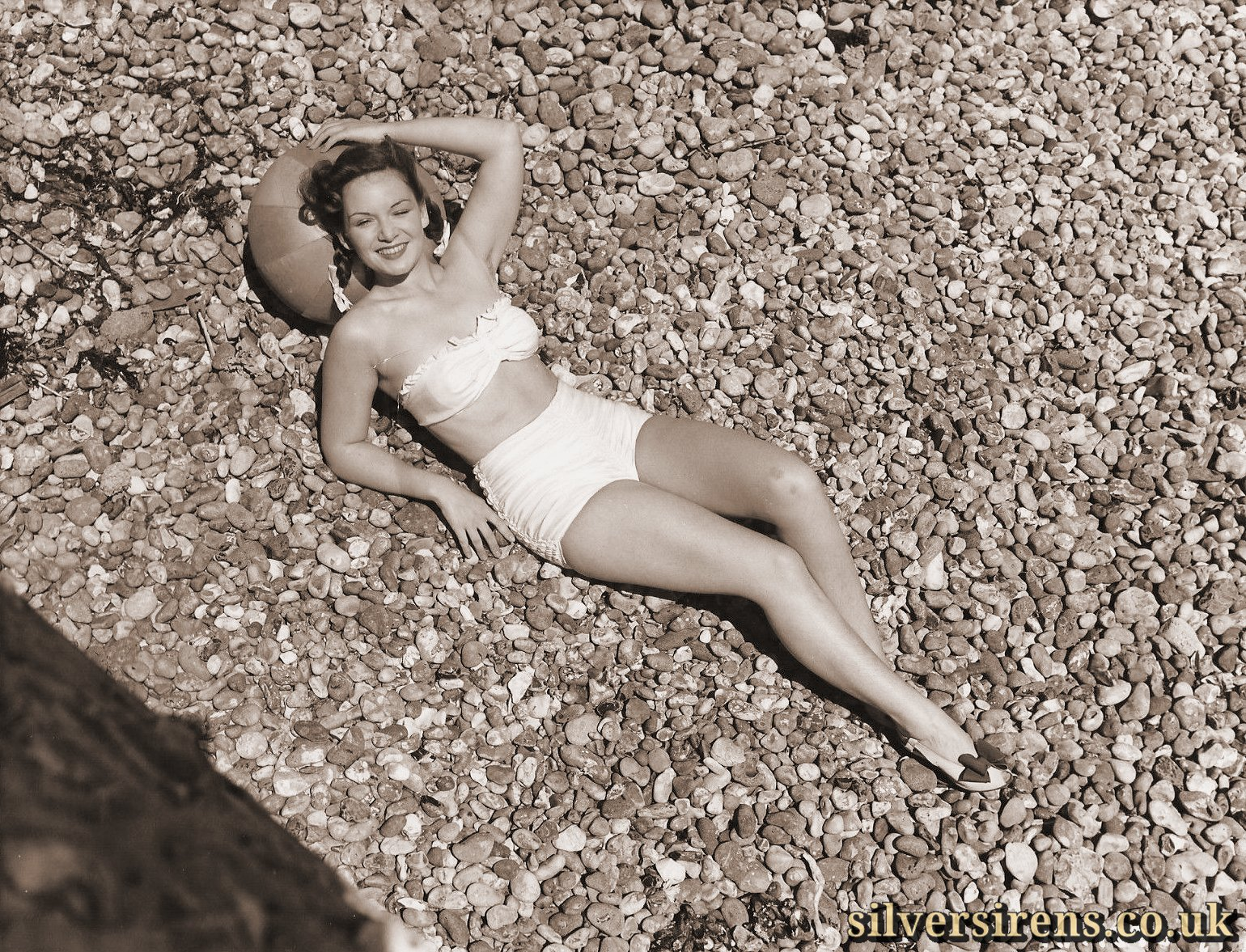 Making the most of the warm weather, Jean Kent, lovely J. Arthur Rank Organisation star, shortly to be seen in Gainsborough's Good Time Girl, sun-bathed on Brighton beach and later took a quick dip.
