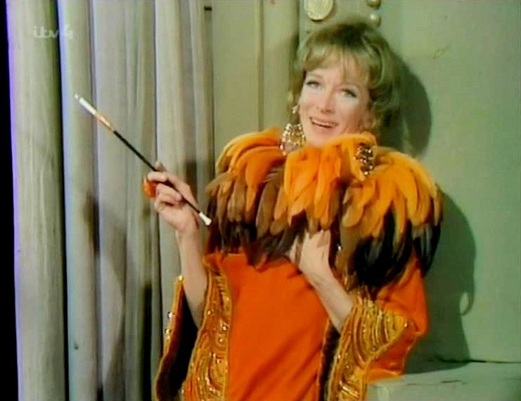 In a 1970 episode of It's Tommy Cooper, British actress Joan Greenwood wears something very orange and feathery!  She holds a cheroot and cigarette for good measure.