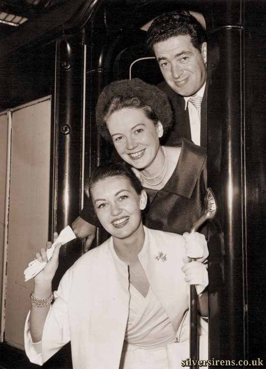 The premiere of the latest Kenneth More comedy Next to No Time will be held on the world's greatest liner Queen Elizabeth at Southampton, and the film loads were taken by special train from Waterloo today.  Much of the film is shot aboard the liner.  Photo shows: Top to bottom: John Gregson, Phyllis Calvert and Janet Scott leave for the premiere.
