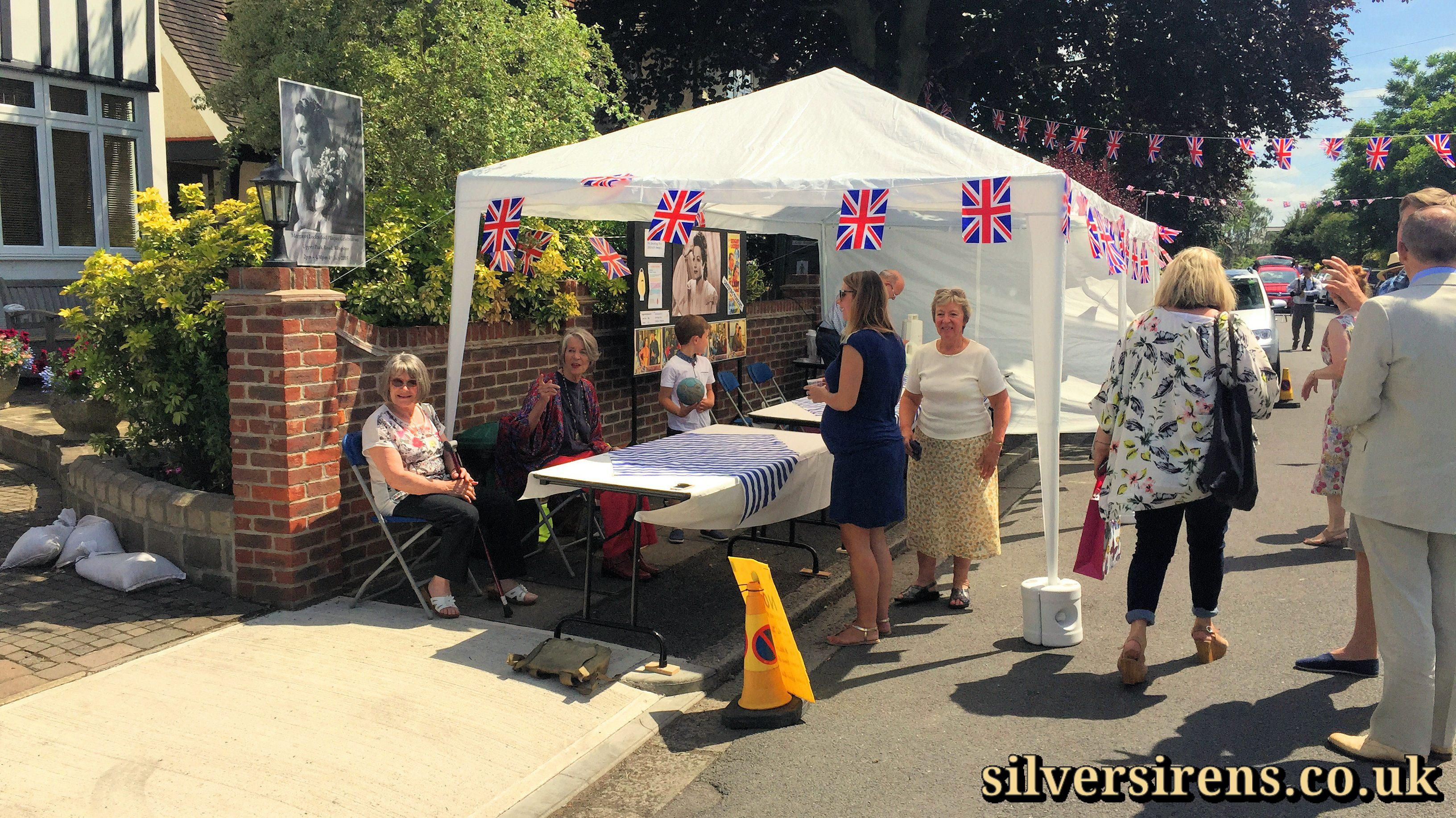 Actress Julia Lockwood (in red trousers) waits in the refreshment tent in Upper Park Road, Kingston for the unveiling of a commemorative blue plaque for her mother, Margaret Lockwood
