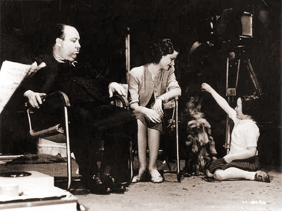 Famous British director Alfred Hitchcock and actress Margaret Lockwood look on as a small child plays on the set of The Lady Vanishes