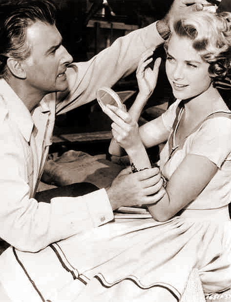 Stewart Granger lends a helping hand to actress Grace Kelly on the set of MGM's Green Fire (1954)