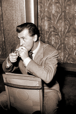 British actor Stewart Ganger lights a cigarette as he sits on a back-to-front chair
