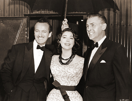 It's raining as they step from the sound stage where they've been enacting a scene for MGM's 'The Little Hut', so Ava Gardner, Stewart Granger and David Niven make use of an umbrella to keep safely dry.