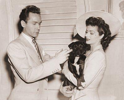 Margaret Lockwood holds aloft a dog for Griffith Jones to pet.