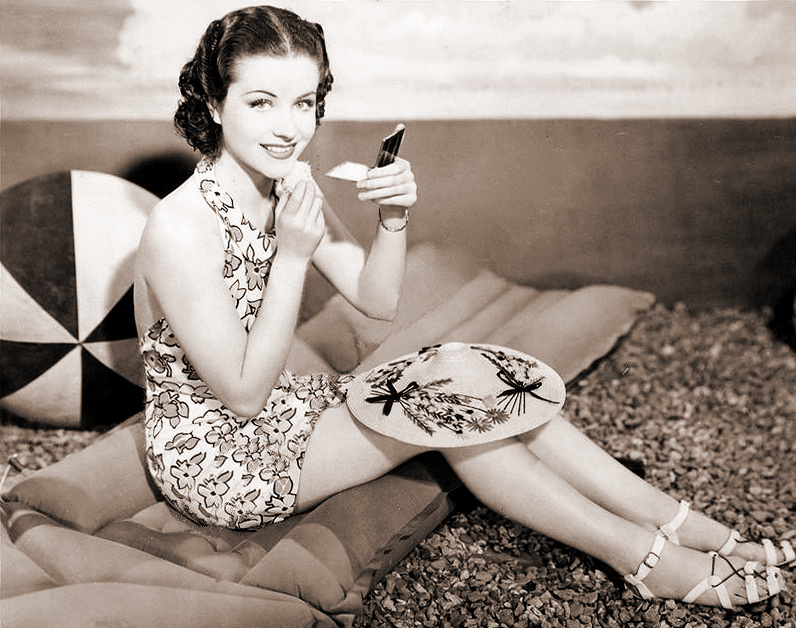 Margaret Lockwood sits on the beach and puts the finishing touches to her make-up.   A publicity shot from Bank Holiday (aka Three on a Weekend).