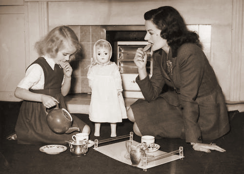 Margaret Lockwood and her daughter Julia Lockwood have tea, watched over by dolly.