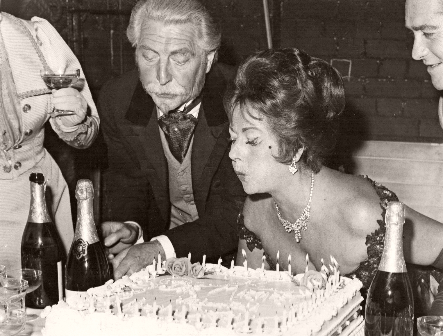 Veteran British film and stage star Margaret Lockwood blows out fifty candles on her birthday cake as her co-star in the play, An Ideal Husband, Roger Livesey, looks on