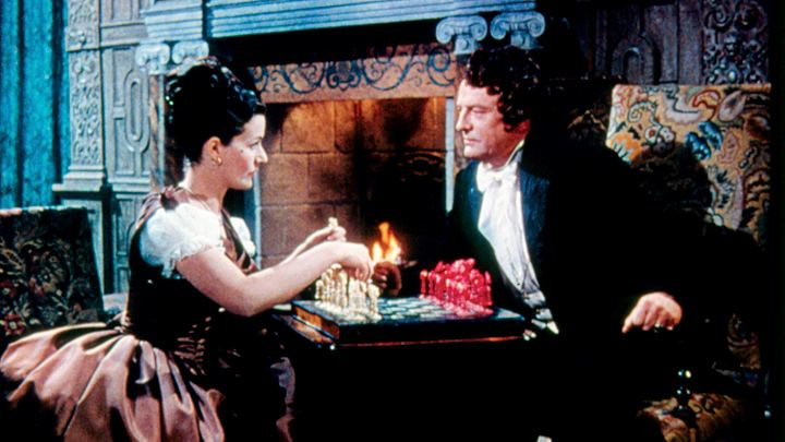 Jassy Woodroffe (Margaret Lockwood) and Nick Helmar (Basil Sydney) play chess in front of the fire at Mordelaine, in the film Jassy (1947)