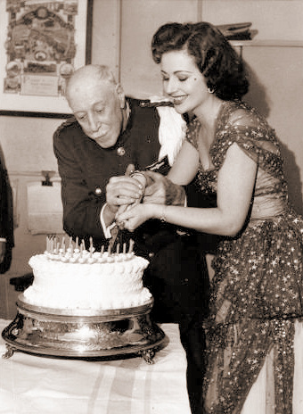 Help is on hand from British actor Arthur Metcalfe as Margaret Lockwood carefully cuts a birthday cake at the Granada Cinema, Willesden on 21st October, 1953.