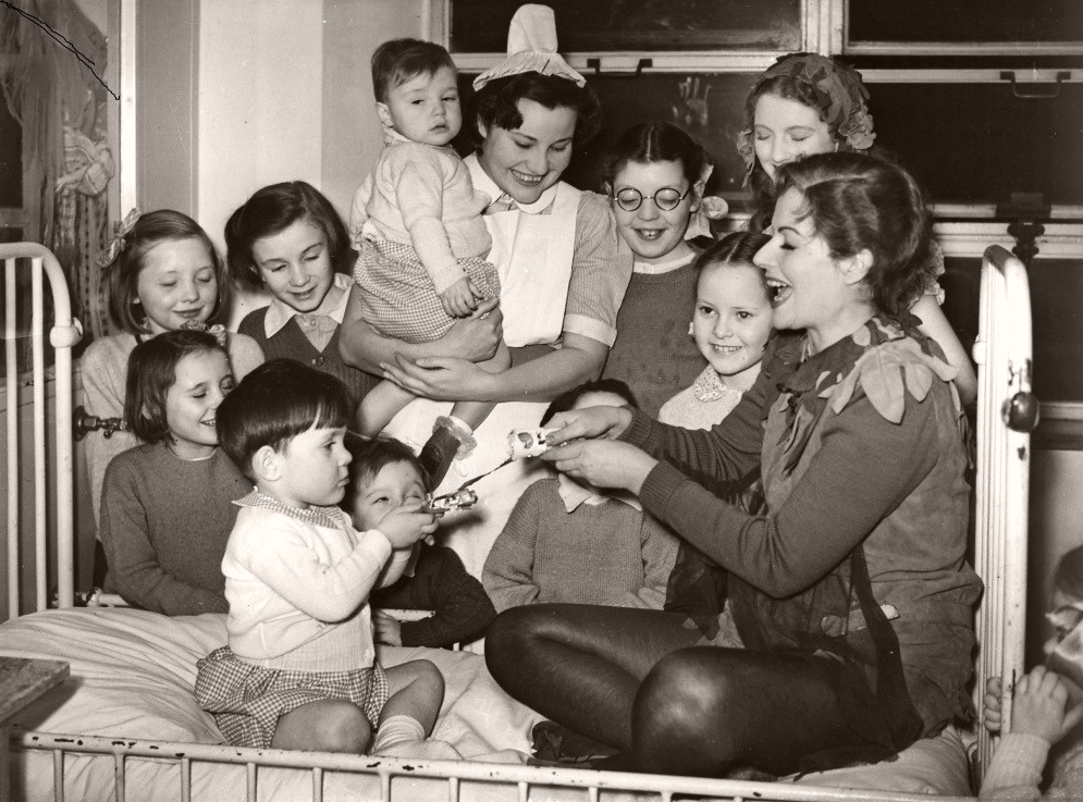 Margaret Lockwood, in costume as Peter Pan, perches on a bed in the ward and laughs as she pulls a cracker with a child at London's Great Ormond Street Hospital in 1949