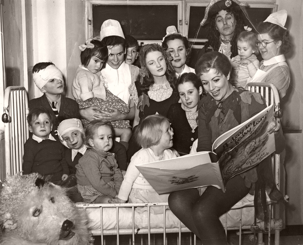 Margaret Lockwood, in costume as Peter Pan, perches on a bed in the ward and reads to the children at London's Great Ormond Street Hospital in 1949