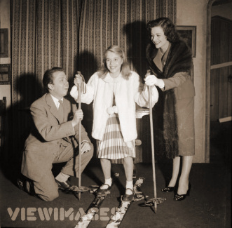 Margaret Lockwood supports her daughter, Julia Lockwood, as she balances on a pair of skis, assisted by actor and director Richard Attenborough (1955)