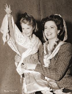 A smiling Margaret Lockwood holds her daughter Julia Lockwood aloft to wave at the crowds