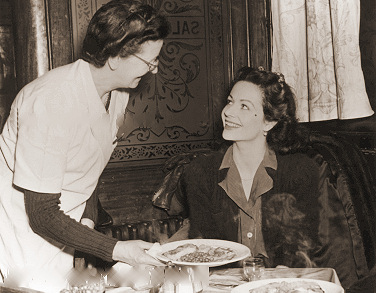 Margaret Lockwood chats with a waitress while being served breakfast in a 1940s cafe