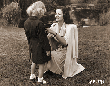 Margaret Lockwood dresses her daughter Julia Lockwood ready for a walk in the park
