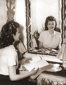 Margaret Lockwood smiles at the camera through the mirror in her dressing room