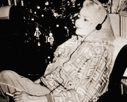 Margaret Lockwood relaxes by listening to music on her Walkman at home, circa 1986.   Next to her is a fully decorated Christmas tree