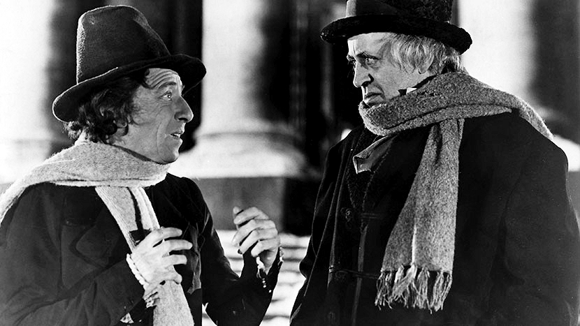 Ebenezer Scrooge (Alastair Sim) looks askance at Bob Cratchit (Mervyn Johns) in a scene from Scrooge (1951)