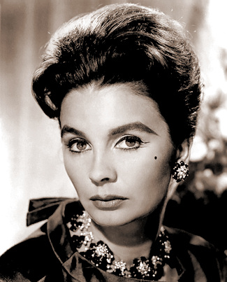 Jean Simmons wears a necklace and earrings