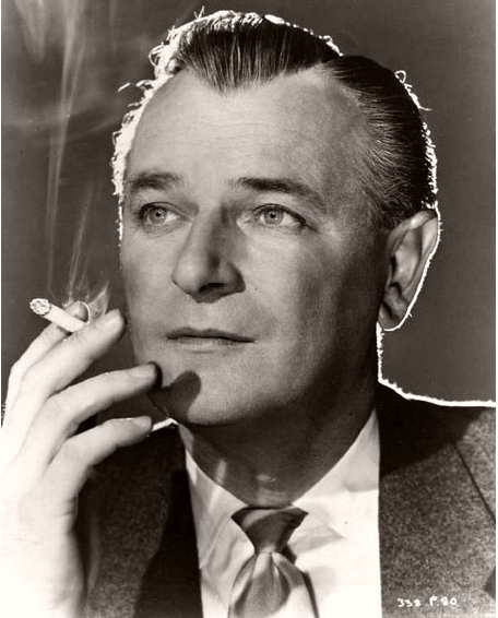 British actor Nigel Patrick, dressed in jacket and tie, smokes a cigarette