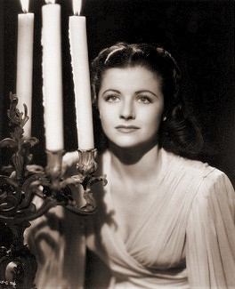 Margaret Lockwood seated behind a large candelabra in Night Train to Munich