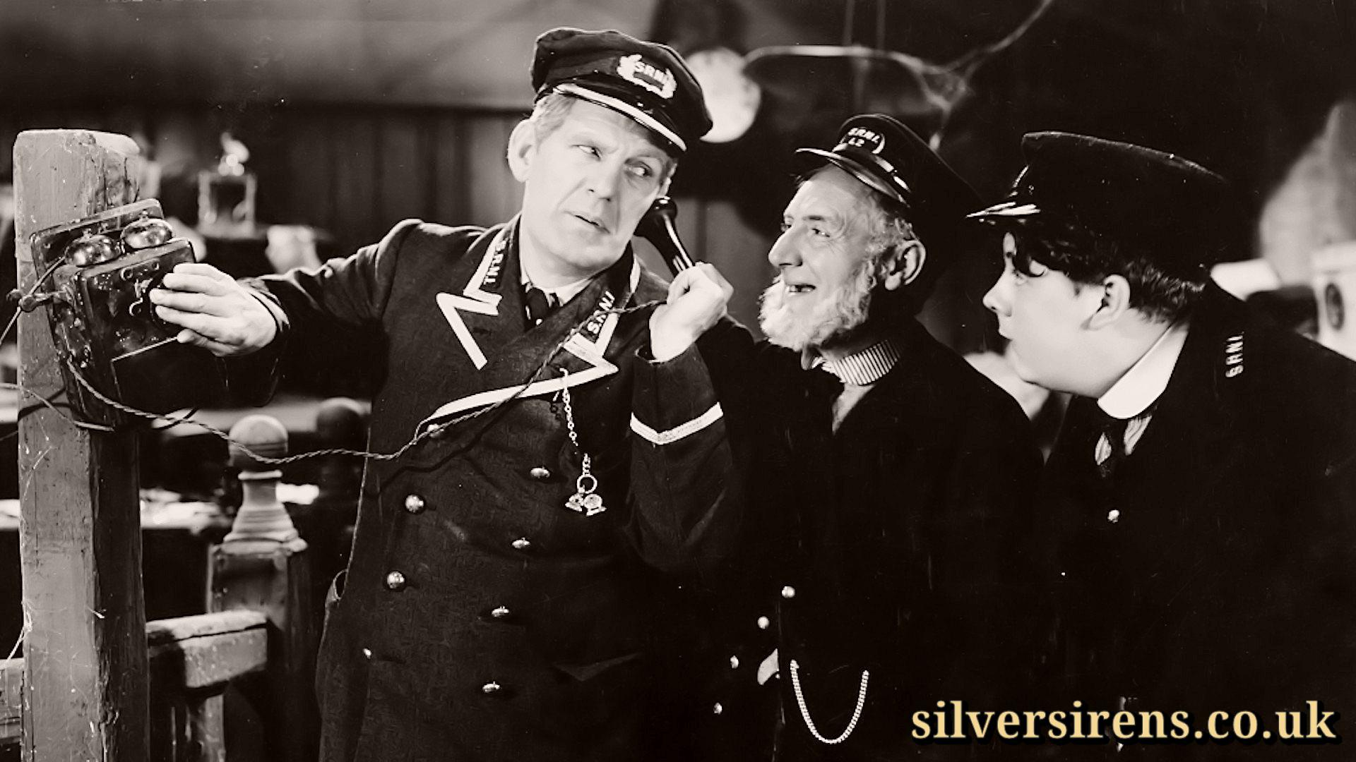 Will Hay (William Porter) on the phone in Oh, Mr Porter! is looked on by Moore Marriott (Jeremiah Harbottle) and Graham Moffatt (Albert)