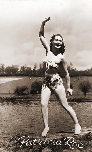 Patricia Roc waves as she wears a bikini and high heels beside a lake