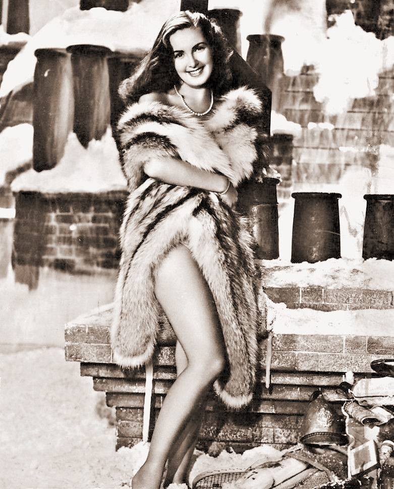 Patricia Roc wears a fur coat in order to try to keep warm amidst the snowy rooftop chimneys