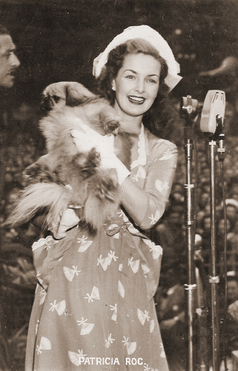 Patricia Roc steps up to the microphones while holding her pet Pekingese dog, Floppy