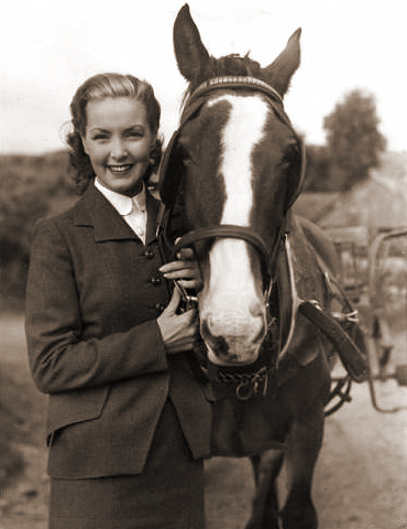 Patricia Roc smiles at the camera while petting her favourite horse