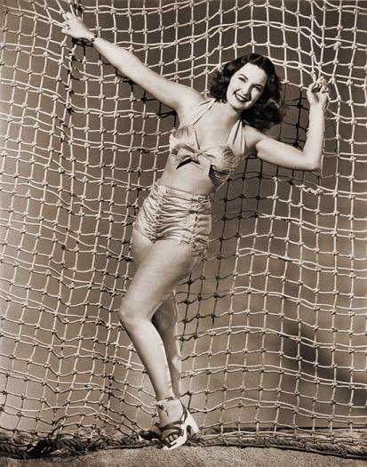 Patricia Roc in a bikini hangs from a net