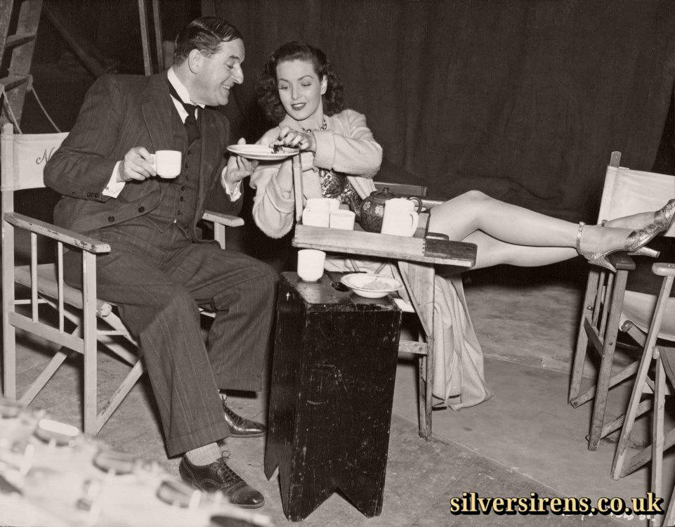 Who could refuse 'the perfect woman'?  Stanley Holloway smiles gallantly while offering the remaining cake on the plate to co-star Patricia Roc, who plays the title role in The Perfect Woman.  An off-set shot from The Perfect Woman, the Two Cities film version of the successful comedy starring Patricia Roc with Stanley Holloway and Nigel Patrick, produced by George and Alfred Black, and directed by Bernard Knowles at Denham.