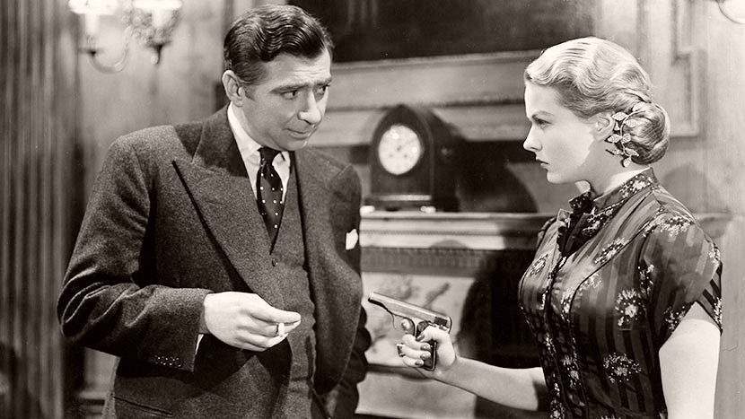 Storm Riordan (Sally Gray) holds a gun to Dr Clive Riordan (Robert Newton) in a scene from Independent Sovereign Films' 1949 film, Obsession
