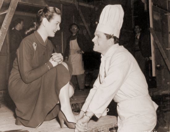 Patricia Roc and Anthony Steel enjoy a joke together on the set of Something Money Can't Buy.    In the film they play husband and wife and he owns a roving restaurant – hence the chef's clothes. <BR><BR> Something Money Can't Buy is a timely comedy of married life in post-war Britain.
